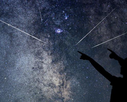 Un ciel avec des étoiles filantes et deux personnes silhouettées qui les regardent