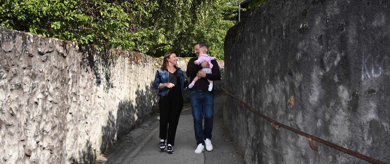 Un jeune couple souriant et complice avec un bébé marche sur le sentier de Pévret.